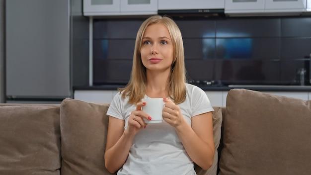 Красивая женщина сидит на диване и смотрит телевизор.