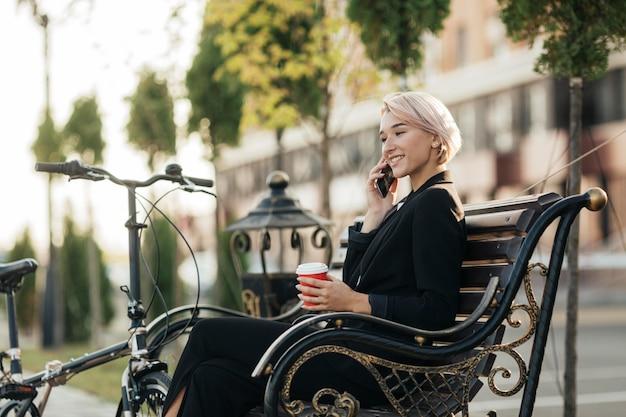 Красивая женщина, сидящая на скамейке