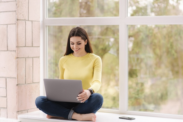 노트북과 woking 창틀에 앉아 예쁜 여자. 집에서 맨발로 프리랜서. 노란색 셔츠에 갈색 머리 여성.