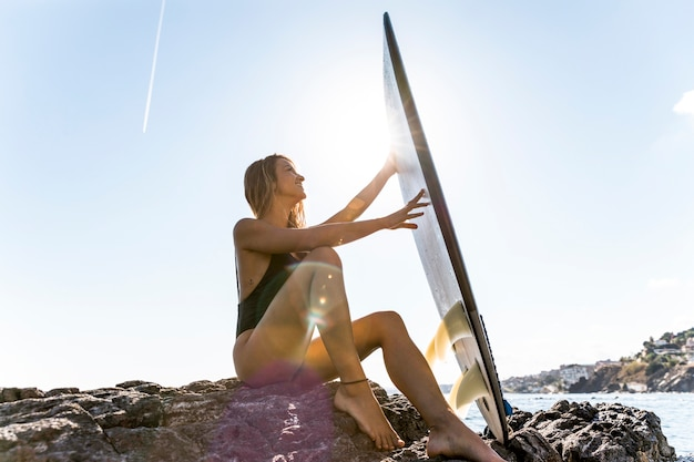 Pretty woman sitting on rocky sea shore with surfboard