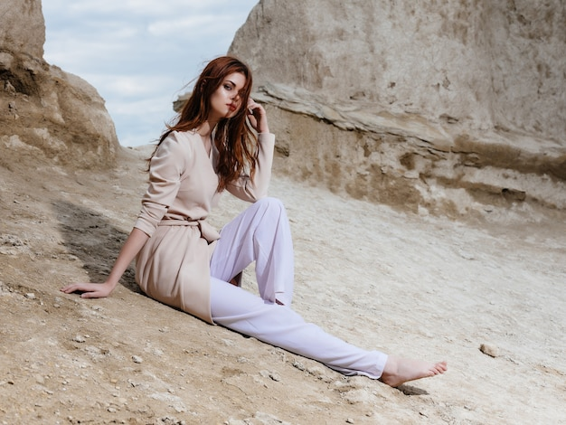 Pretty woman sitting on the sand attractive look. high quality photo