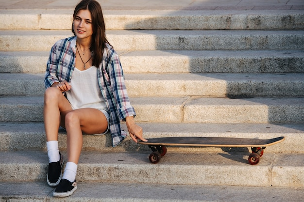 Pretty woman sitting on the stairs next to her skateboard under a gentle sun