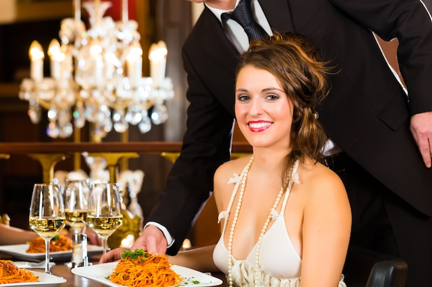 Pretty woman sitting at a table in a fine dining restaurant, waiter served the dinner, a large chandelier is in