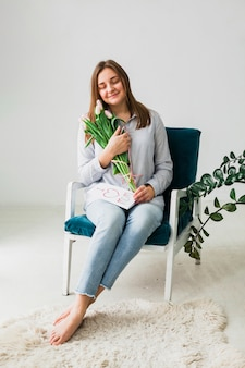 Pretty woman sitting with tulips and greeting card
