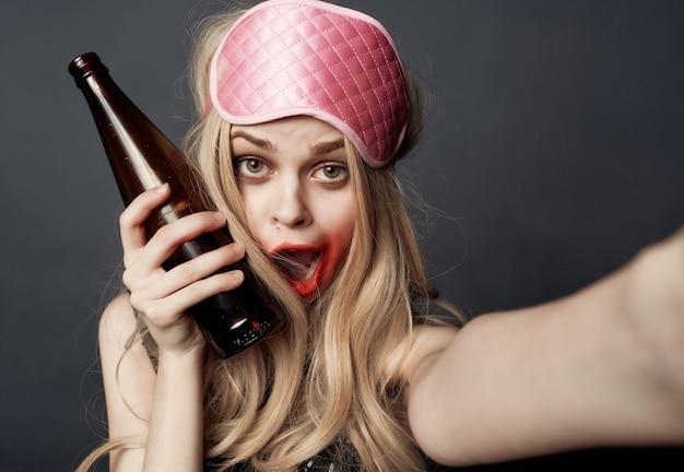 きれいな女性が口紅を塗ったナイトライフアルコールボトル孤立した背景