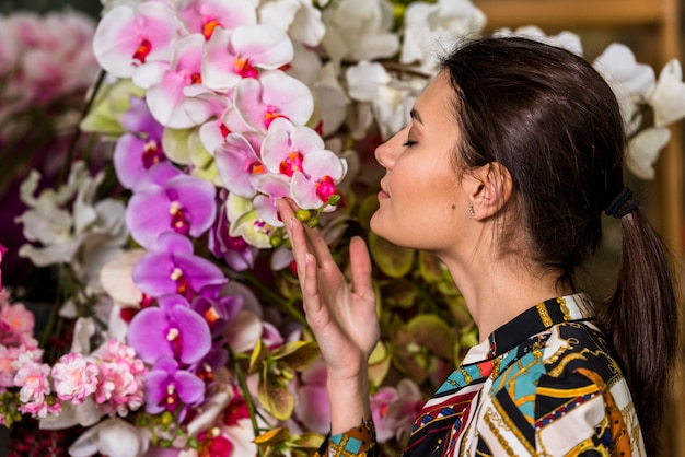 Pretty woman smelling pink flowers in green house