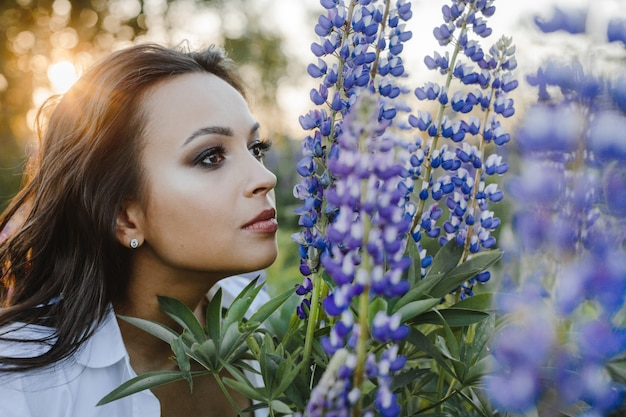 Pretty woman smells a bouquet of lupines