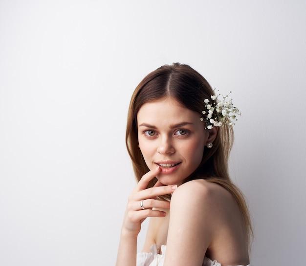 きれいな女性は彼女の髪に失望の装飾の花を笑顔します。高品質の写真