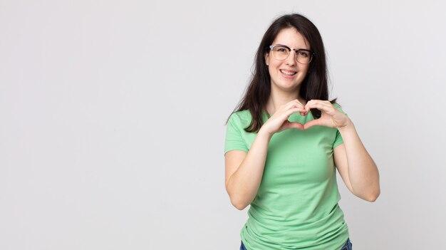 笑顔と幸せ、かわいい、ロマンチックな恋を感じ、両手でハートの形を作るきれいな女性