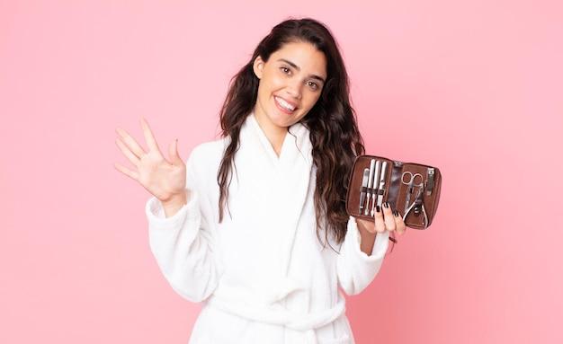 Симпатичная женщина улыбается и выглядит дружелюбно, показывает номер пять и держит сумку для макияжа с инструментами для ногтей