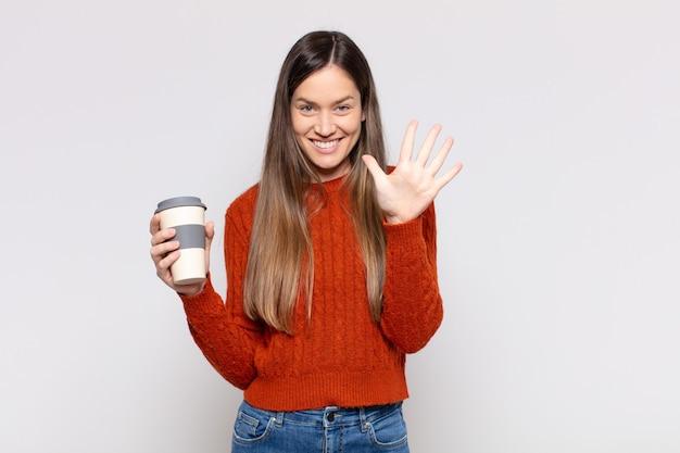 笑顔でフレンドリーに見えるきれいな女性、前に手を前に5番または5番を示し、カウントダウン