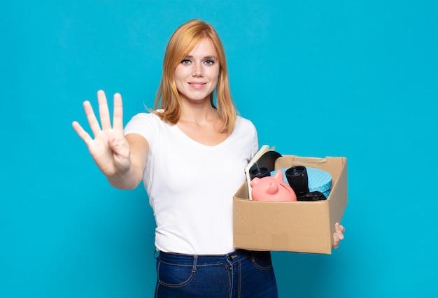 Симпатичная женщина улыбается и выглядит дружелюбно, показывает номер четыре или четвертый с рукой вперед, отсчитывая