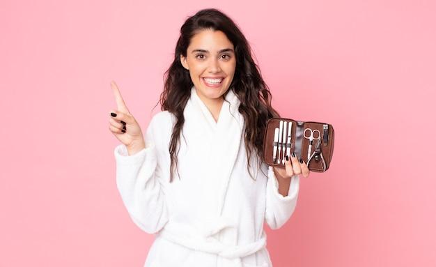 Красивая женщина улыбается и выглядит дружелюбно, показывает номер один и держит сумку для макияжа с инструментами для ногтей
