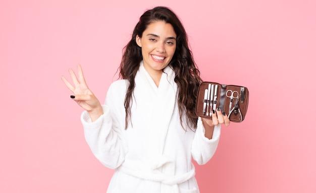 Красивая женщина улыбается и выглядит дружелюбно, показывает номер три и держит сумку для макияжа с инструментами для ногтей