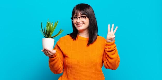 笑顔でフレンドリーに見えるきれいな女性、前に手を前に3番目または3番目を示し、カウントダウン