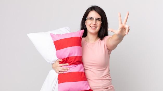 笑顔でフレンドリーに見えるきれいな女性、パジャマを着て枕を持って3番目を示しています