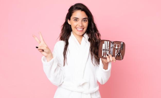 Красивая женщина улыбается и выглядит дружелюбно, показывает номер два и держит сумку для макияжа с инструментами для ногтей