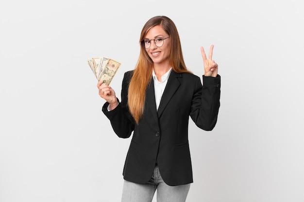 Симпатичная женщина улыбается и выглядит дружелюбно, показывая номер два. бизнес и концепция долларов