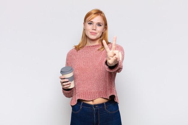 Симпатичная женщина улыбается и выглядит дружелюбно, показывает номер два или секунду рукой вперед, отсчитывая