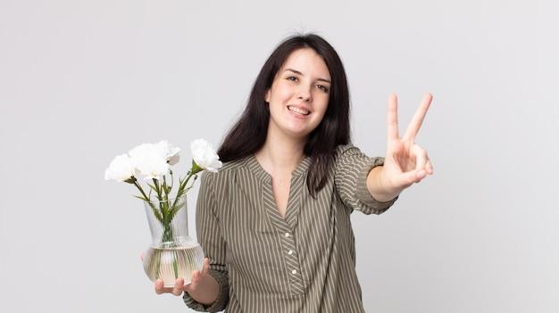 笑顔で幸せそうに見えるきれいな女性、勝利または平和を身振りで示し、装飾的な花を持っています。ヘッドセット付きのアシスタントエージェント