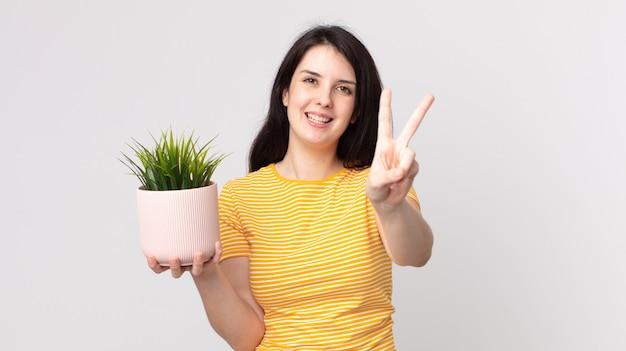 Красивая женщина улыбается и выглядит счастливой, жестикулирует победу или мир и держит декоративное растение