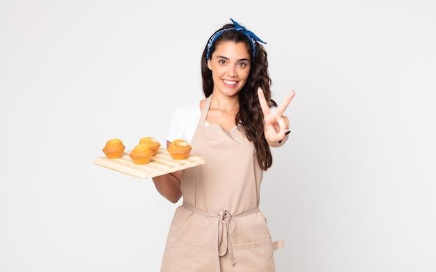 Красивая женщина улыбается и выглядит счастливой, жестикулирует победой или миром и держит поднос с кексами
