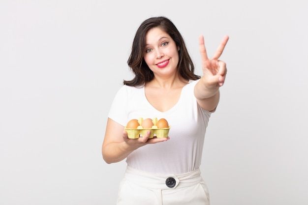 Красивая женщина улыбается и выглядит счастливой, жестикулирует победой или миром и держит коробку для яиц