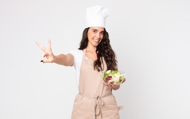 Красивая женщина улыбается и выглядит счастливой, жестикулирует победой или миром в фартуке и держит салат