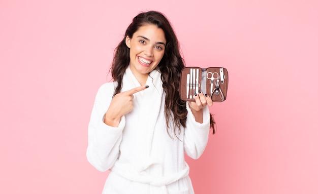 Красивая женщина весело улыбается, чувствует себя счастливой и указывает в сторону и держит сумку для макияжа с инструментами для ногтей