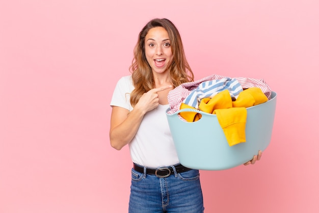 元気に笑って、幸せを感じて、横を指して、服を洗うきれいな女性。