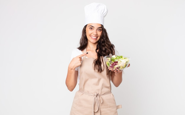 Красивая женщина весело улыбается, чувствует себя счастливой и указывает в сторону в фартуке и держит салат