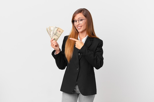 Pretty woman smiling cheerfully, feeling happy and pointing to the side. business and dollars concept