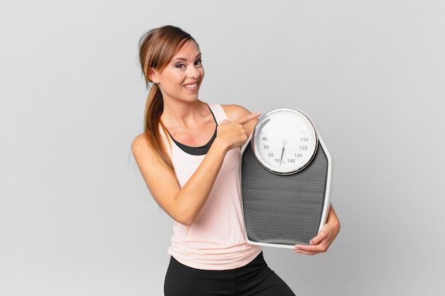 Pretty woman smiling cheerfully, feeling happy and pointing to the side. diet concept