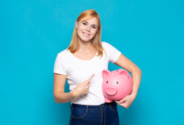 Pretty woman  smiling cheerfully, feeling happy and pointing to the side and upwards, showing object in copy space