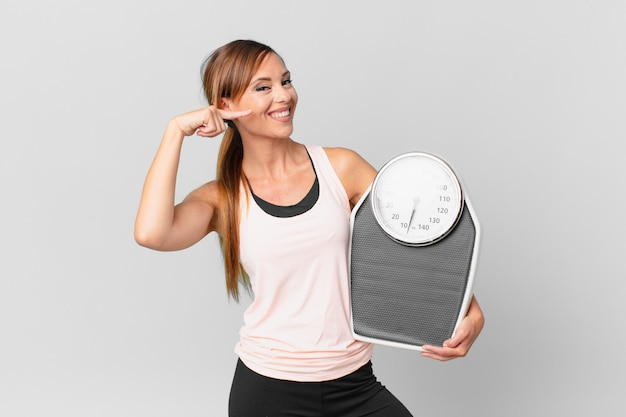Pretty woman smiling confidently pointing to own broad smile. diet concept