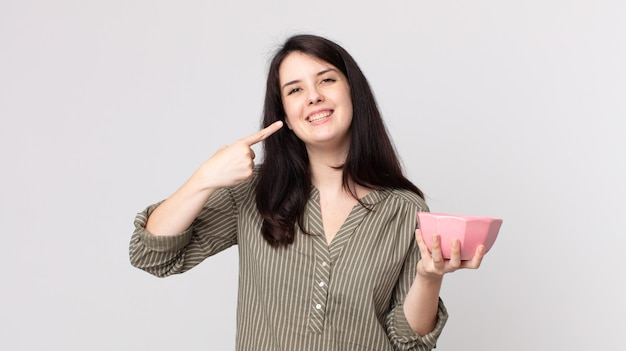 Pretty woman smiling confidently pointing to own broad smile holding an empty pot bowl. assistant agent with a headset