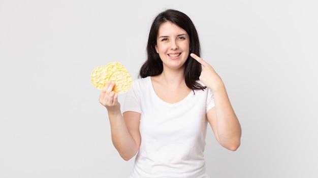 Красивая женщина улыбается, уверенно указывая на собственную широкую улыбку и держа в руках диетические рисовые лепешки