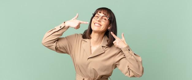 自信を持って笑顔のきれいな女性は、自分の広い笑顔、前向きで、リラックスした、満足のいく態度を指しています