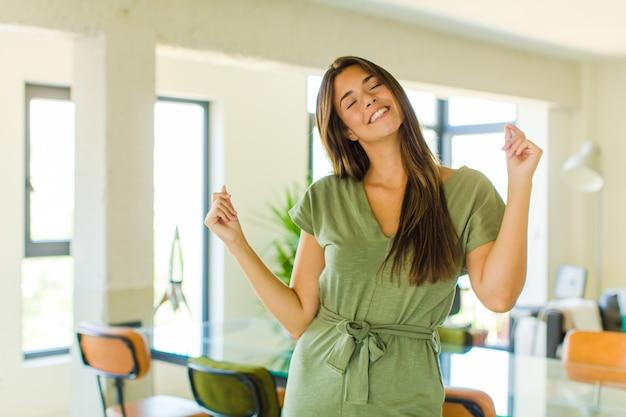 Красивая женщина улыбается, чувствует себя беззаботной, расслабленной и счастливой, танцует и слушает музыку, веселится на вечеринке