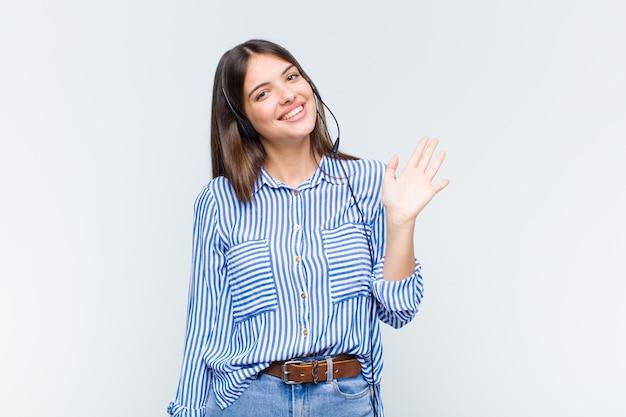행복하고 유쾌하게 웃고, 손을 흔들며, 환영하고 인사하거나 작별 인사를하는 예쁜 여자