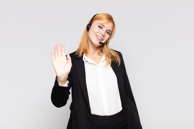 幸せで元気に笑って、手を振って、あなたを歓迎して挨拶するか、さようならを言うきれいな女性