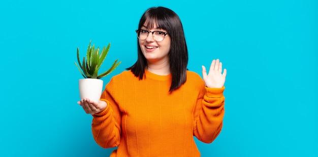 Красивая женщина счастливо и весело улыбается, машет рукой, приветствует и приветствует вас или прощается