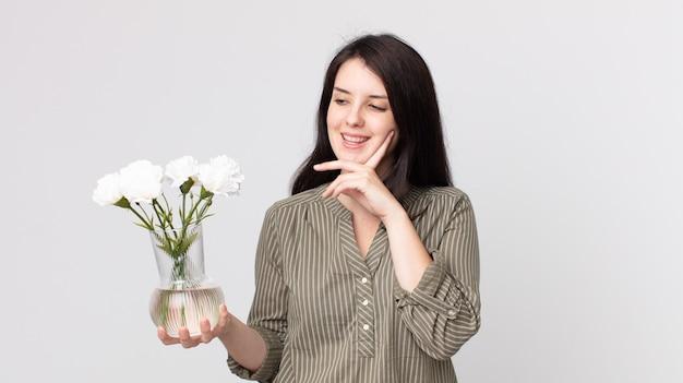 Красивая женщина счастливо улыбается и мечтает или сомневается и держит декоративные цветы. помощник агента с гарнитурой