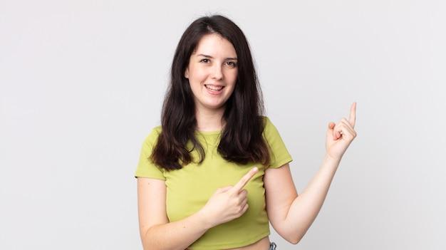 Красивая женщина счастливо улыбается и показывает в сторону и вверх обеими руками, показывая объект в копировальном пространстве
