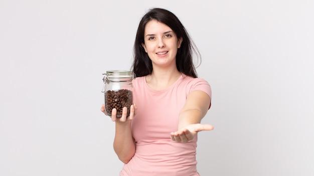 예쁜 여자가 친절하게 웃으며 개념을 제시하고 커피 콩 병을 들고 행복하게 웃고 있습니다.