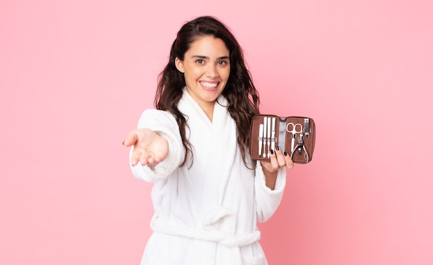 Красивая женщина счастливо улыбается, дружелюбно предлагает и показывает концепцию и держит сумку для макияжа с инструментами для ногтей