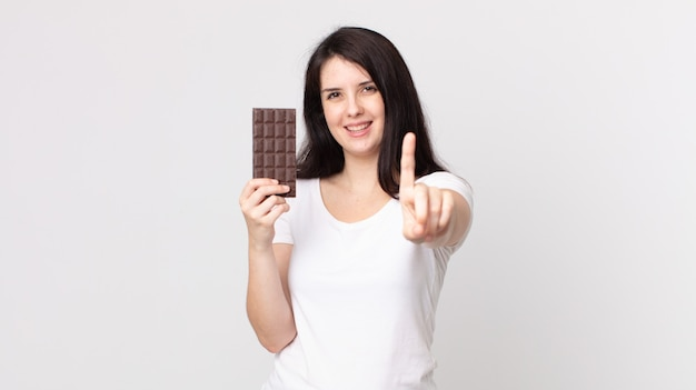 誇らしげに笑顔で自信を持ってナンバーワンを作り、チョコレートバーを持っているきれいな女性