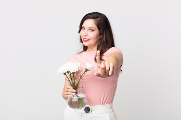 Красивая женщина, гордо и уверенно улыбаясь, делает номер один и держит в руках декоративный цветочный горшок