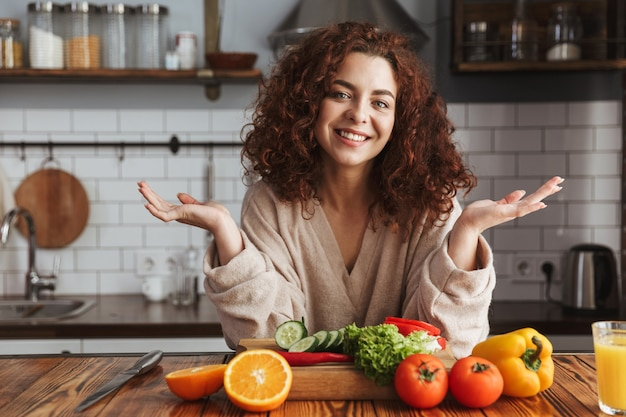 Pretty woman smiling while cooking salad with fresh vegetables in kitchen interior at home