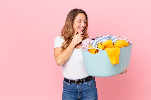 あごに手を当てて、服を洗う幸せで自信に満ちた表情で笑っているきれいな女性